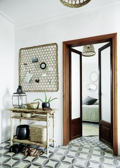 Make a big impact with a tiled entryway. This one features a geometric black, white and gray pattern. A basket hangs on the wall as a unique bulletin board idea, and a table below catches shoes, keys and other things as you walk in the door.