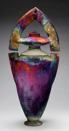 Raku Vessel. Raku began in Japan and was hand-made pottery fired at a low temperature. Today, Raku can also mean pottery fired at a low temperature, then moved while still hot into a container with combustible materials such as sawdust or paper that burn onto the pottery to make patterns or colors on the surface of the pottery.