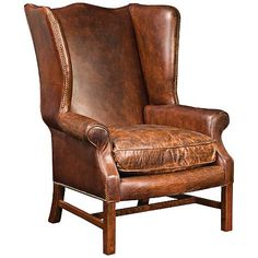 A handsome wingback arm chair with cigar brown top-grain leather upholstery and nailhead trim.