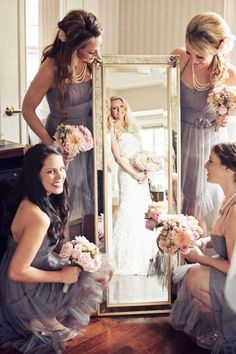 Wedding picture idea: bridesmaids hold a mirror with the bride reflected in it so it looks like a picture frame.