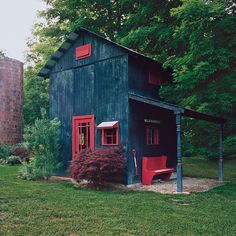 outbuilding with dark blue vertical plank siding, bright red trim, door and bench with a red-handled pitch fork to accessorize. Small house home cottage cabin. Cabana, Potting Sheds, She Sheds, Cabins And Cottages, Tiny Spaces, Cabins In The Woods, Little Houses, Play Houses, Architecture