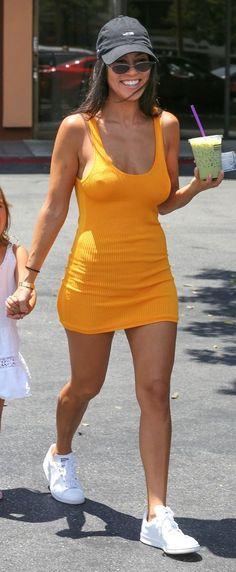 Kourtney Kardashian wears an affordable H&M yellow mini dress, dad hat and Stan Smiths making for an instantly cool look.