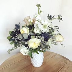 A wedding centerpiece for a round table made with scabiosa, garden roses, snowball hydrangea, roses, stock and thistle