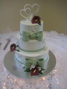 This is the wedding cake I did for my nephew and his new wife, It is Sage & Burgundy 6,8,10 in. rounds, iced in BC with fondant/gumpaste decorations. Thank You to Sharon (Sugarshack) for her Boxes & Bows DVD. Edna (Tonedna) for her youtube video on making Calla Lillies. The 3 lines with a jewel at the ends, represets the groom, bride and a son as a family (I did this on another wedding cake for the same reason) they all love this idea. There are jewels in some of the flowers. Last min. h