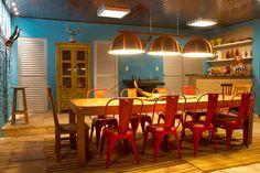 Restaurante. A decoração do ambiente de 90 m² tem itens típicos da cidade histórica de Pirenópolis (GO), como os bustos femininos multicoloridos e as máscaras em formato de cabeça de boi, usadas na festa da Cavalhada. A parede lateral não tem reboco – só chapisco. O chão recebeu tapetes de sisal. A iluminação é feita com lâmpadas minidicróicas, paflons e um pendente com três cúpulas. Ambiente criado pelos arquitetos Fábio Guedes e Julianny Xavier.