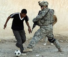 Spc. Eric Alfredsen, from the U.S. Army's 101st Airborne Division Air Assault, plays soccer with a youth in Beiji, Iraq.