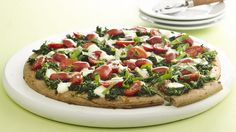 Top this simple spinach pizza with the sweetness of lightly marinated grape tomatoes and pearls of fresh mozzarella cheese.