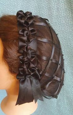 A pretty ribbon hairnet suitable for both day and evening wear. The black coloring of this hairnet makes it the perfect accessory for your Mourning attire. Our pretty ribbon hairnet features your choice of a coronet of folded ribbons as listed below. The net itself is of black satin