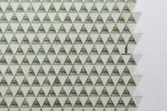 """artwork made from the """"all-seeing eye"""" triangle cut out of 114,000 US dollar bills"""