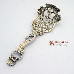 American sterling silver large candy or nut spoon that features ornate openwork fleur-de-lis, scroll, and shell openwork decorations. The spoon is entirely gilt. Made by Redlich & Co. c.1890. Marked 705.
