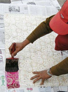 Instead of dipping a block in color, the artist dips a block in liquid wax and then prints on the paper. Once the paper is dry, the artist paints the paper with color and irons the paper to remove the wax.  You will have a stunning Batik gift paper!! -Green Elephant