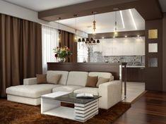 Keskeny pult választja el a kényelmes nappali ülőgarnitúrát az ultramodern konyhától. A négyzetalapú konyha mennyezetét két szabálytalan fényárok töri meg.