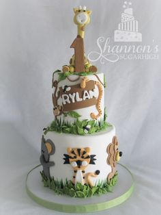 2-tier zoo theme cake for a little boy turning 1! Red velvet cake with cream cheese flavour buttercream, white chocolate ganache, and fondant. Animals include monkey, snake, elephant, tiger, lion, and giraffe cake topper. Cake inspired from Jungle Cake by CakeHeaven by Marlene. Keywords: jungle, birthday, boy.