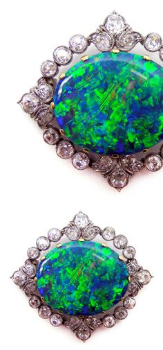 Early 20th century opal and diamond brooch, c 1905, the central blue green opal in gold claw mount, to an old brilliant-cut diamond border, set in platinum, with trefoil detail at the cardinal points, gold pin fitting to the reverse.  At SJ Phillips.