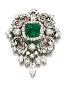 Emerald and diamond brooch / pendant. Of scroll design, set with a cabochon emerald, single-, brilliant-cut and pear-shaped diamonds.