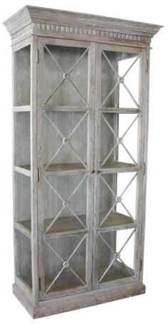 A white washed French style display cabinet featuring glass doors with an X design. It has glass on all three sides giving this piece lots of light and impact f
