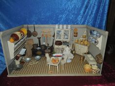 Beautiful antique German dollhouse kitchen, ca. 1910. Size: 75 cm x D: 47 cm x H: 37 cm.  The furniture is probably Gottschalk.  The cook is a Biedermeier doll.