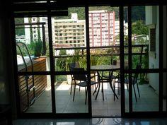 Porta anti-ruído em esquadria de alumínio com vidros acústicos de acesso da sala para varanda. Instalada em Teresópolis, RJ
