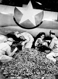 Removing spent shell casings from a B-17 after a completed mission.