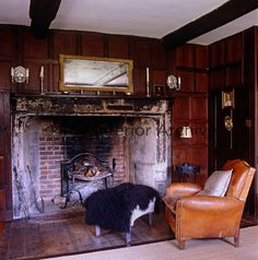 A leather armchair sits in front of a large stone Tudor fireplace in this wood panelled living room.
