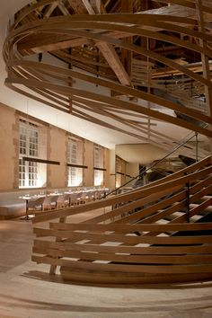 Brasserie Les Haras in Strasbourg, France - spiral of wooden strips surrounds a staircase in the restaurant of this Strasbourg hotel, designed inside a former equestrian academy - Interior design by Paris studio Jouin Manku