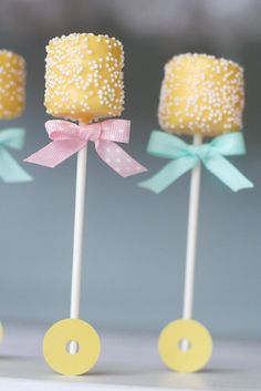 To make these baby rattle pops, begin with candy coated marshmallow pops decorated with sprinkles. Tie on (or adhere with a glue dot) little bows to each.