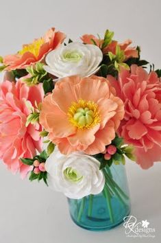 Coral peonies, peach poppies, white ranunculus, in an aqua mason jar