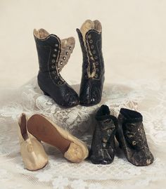 """Three Pairs of French Doll Shoes Signed Huret    Suitable for classic Huret poupee,16""""–17"""" (40–43 cm). Includes black kidskin boots with wooden heels,eight pairs of brass lacing grommets (no laces); ivory silk ball slippers with silk covered wooden heels; and brown ankle boots with wooden heels and three gold buttons on each. Each with border-outlined soft kidskin soles stamped Huret A Paris. Good condition. Circa 1860."""