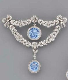{Brooch Only} A BELLE EPOQUE SAPPHIRE AND DIAMOND BROOCH AND A PAIR OF EAR PENDANTS The central circular-cut sapphire and diamond cluster drop within the rose-cut diamond floral wreath with diamond bow terminals, suspending a sapphire and diamond drop, earrings en suite, adapted, mounted in platinum, circa 1905.
