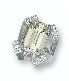 Diamond ring. Set with an emerald-cut diamond weighing 23.09 carats, to a stylised mount highlighted by baguette diamonds together weighing approximately 1.60 carats, mounted in 18 karat white gold.