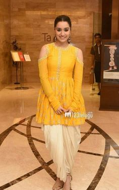 2018 Indian Fashion: Shraddha Kapoor in a peplum style kurt and dhoti style salwaar in mustard yellow and cream. via 2018 Indian Fashion: Shraddha Kapoor in a peplum style kurt and dhoti style salwaar in mustard yellow and cream. Indian Gowns Dresses, Indian Fashion Dresses, Dress Indian Style, Indian Designer Outfits, Party Wear Indian Dresses, Indian Outfits, Fashion Outfits, Dhoti Salwar Suits, Churidar