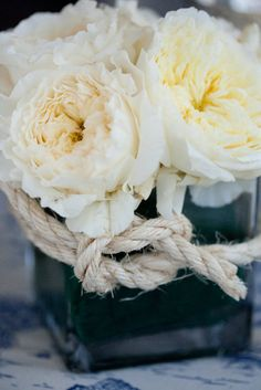 Love the simplicity and the old-fashioned roses and simple holder (and height, that doesn't block people's conversation!)-- and the rope-tied detail.  Works well for the nautical feel without being too cutesy.