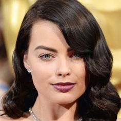 Margot Robbie debuts a new, dark hair color and a deep, plum lip. Get the look here.