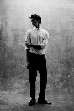 High contrast, blown out blacks and whites. Rustic gray background. Casual stance, business casual clothing. Emphasizing his length by raising his chin and having him look sideways
