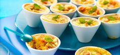 (voor 12 stuks) Verwarm de oven voor op th. 6 – 180°C. Smeer 12 minisoufflékommetjes in met boter. Halveer de kerstomaten, meng met garnalen en fijngehakte basilicum. Verdeel over de kommetjes. Meng de bloem en 1 ei met de garde. Voeg de overige eieren en room toe; breng op smaak met peper en zout. Giet in de kommetjes. Bak 15 min. in de oven. Dien warm of koud op, versierd met een basilicumblaadje. Variant: Je kan de garnalen vervangen door g...