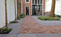 Mooie stadstuin met oud hollandse tuintegels en gebakken sierbestrating.
