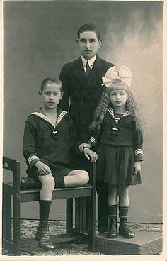 Sarah or Lillian on right. An older boy and his younger siblings in sailor suits,