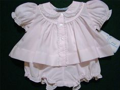 This lovely Hand~Embroidered  newborn two piece topper set has short elasticized puffed sleeves and white embroidery, fagoting and French lace trim on the collar. It has lace trim down the button front and gathering below the yoke adding lots of fullness. The matching bottoms have an elasticized waist and elasticized ruffled leg openings