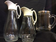 LOT OF THREE GLASS SYRUP DISPENSERS OR CREAMERS. THEY MEASURE 5 TO 9 INCHES HIGH.