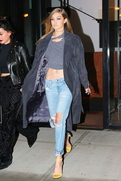 Gigi Hadid adds a pop of color to her gray + denim outfit with yellow sandals.