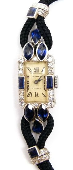 Art Deco sapphire and diamond lady's wristwatch by Cartier, Paris c.1925 , the cream rectangular dial with black Roman numerals, diamond set bezel with rectangular cut sapphires to either side, three sapphires of marquise and pear shape forming a triangle at the shoulders, on a black cord strap with sapphire and diamond toggles, black enamel and gold deployant clasp, the case and toggles mounted in platinum