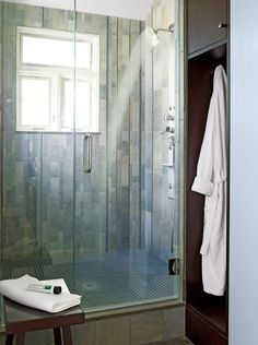 This shower showcases texture and contrast with porcelain tiles of varying sizes covering the walls. Blue mosaic glass tiles line the shower floor and appear as accents on the wall. #walkinshower #walkinshowerideas #bathroommakeover #showerideas #bhg Window In Shower, Glass Shower Doors, Shower Floor, Walk In Shower, Shower Walls, Bathroom Renos, Bathroom Flooring, Small Bathroom, Bathroom Ideas