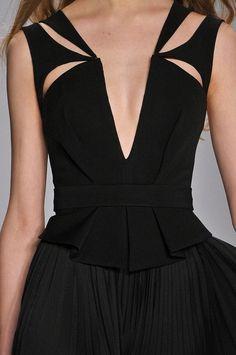 J. Mendel: symmetrical cut-away shapes work to soften neckline and solid black gown. DETAILS