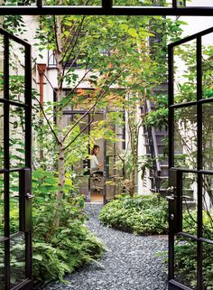 Steel doors leading to a small #courtyard with pebble pavers and lots of #nature