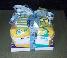 "A book for baby on the bottom (instead of a card), bag of diapers in the middle, zip up jammies on top all tied together with twine and ""it's a boy"" ribbon. Easy/cheap/adorable baby shower gift!"