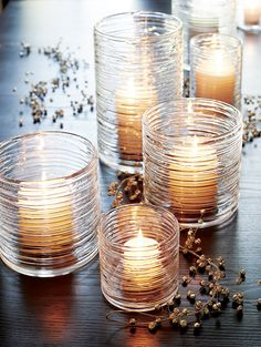 Spun glass cylinders with distinctive organic texture create a dramatic candlelight glow or showcase for fresh flowers.