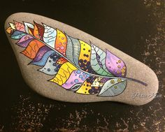 Very pretty designed feather painted on stone!