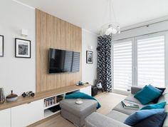 salon clair en blanc et gris avec un panneau mural en bois, écran plasma et meuble TV bac en bois et en blanc
