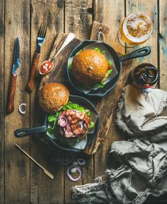 #Beef burgers in cast iron pans  Homemade beef burgers with crispy bacon and vegetables in small cast iron pans and glass of wheat beer on rustic board over shabby wooden background top view vertical composition