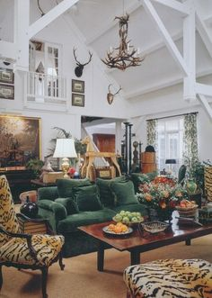 Rustic, cozy elegance - green velvet couch, leopard chair and ottoman, antlers, beams, oil painting